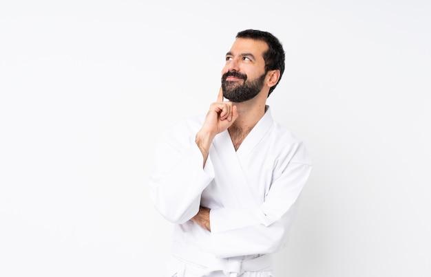 Junger mann, der karate über lokalisierter weißer wand denkt eine idee beim oben schauen tut