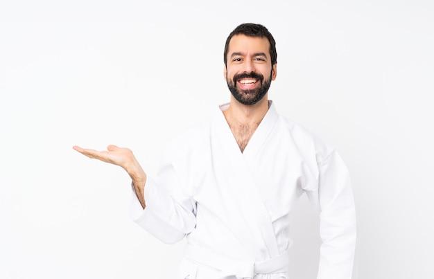 Junger mann, der karate über lokalisierter weißer wand hält copyspace eingebildet auf der palme tut, um eine anzeige einzufügen