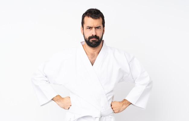 Junger mann, der karate über weißem verärgertem tut
