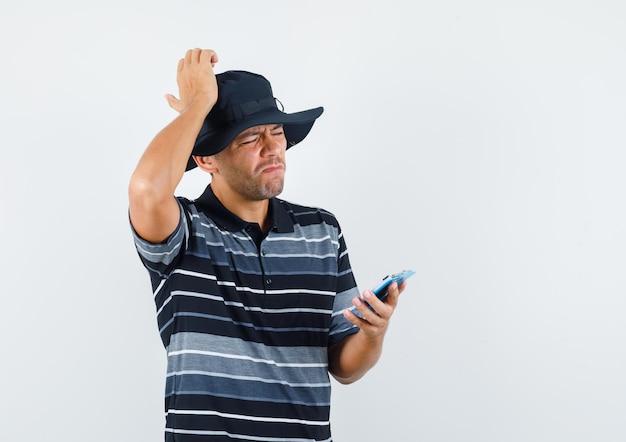 Junger mann, der klemmbrett mit der hand auf dem kopf im t-shirt, im hut hält und bedauert. vorderansicht.