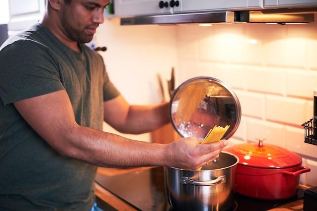 Junger mann, der köstliche gerichte zubereitet