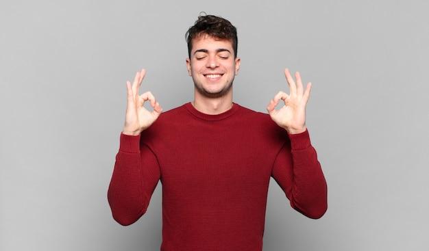 Junger mann, der konzentriert und meditierend aussieht, sich zufrieden und entspannt fühlt, denkt oder eine wahl trifft