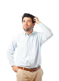 Junger mann, der kopf auf einem weißen hintergrund verkratzt