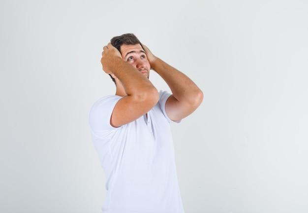 Junger mann, der kopf in den händen hält und im weißen t-shirt oben schaut und besorgt schaut