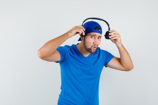 Junger mann, der kopfhörer im blauen t-shirt und in der vorderansicht der kappe trägt.