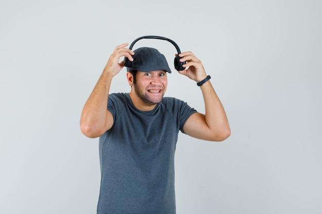 Junger mann, der kopfhörer im t-shirt, in der mütze trägt und lustig schaut. vorderansicht.