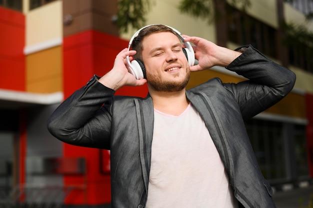 Junger mann, der kopfhörer mit seinen händen hält