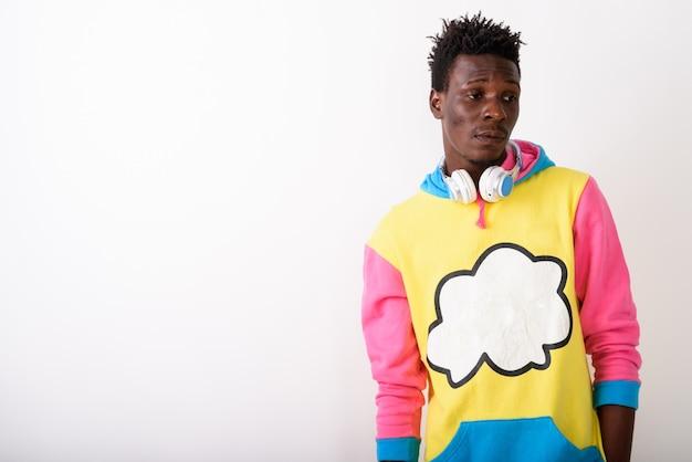 Junger mann, der kopfhörer und buntes sweatshirt denkt und trägt