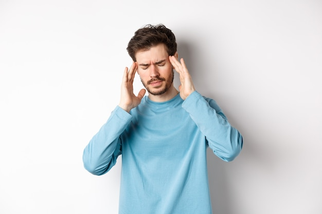Junger mann, der kopfschmerzen oder kater hat, die schläfen berührt und die stirn runzelt, sich von migräne krank fühlt und auf weißem hintergrund steht