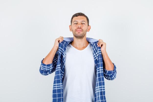 Junger mann, der kragen der kleidung im hemd hält und zuversichtlich, vorderansicht schaut.
