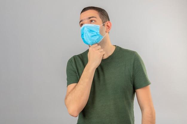 Junger mann, der krank sieht, die medizinische gesichtsmaske hält, die hände auf seinem hals wegen des auf weiß isolierten halsschmerzes hält