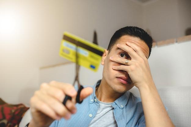 Junger mann, der kreditkarte mit schere schneidet. homebanking und technologiekonzept.
