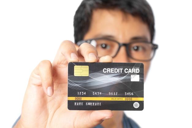 Junger mann, der kreditkarte zeigt.