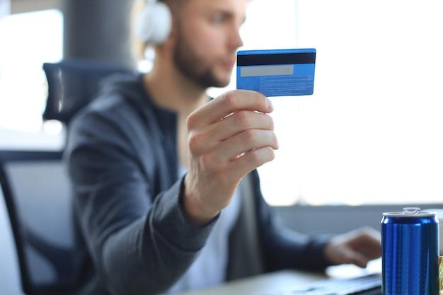 Junger mann, der kreditkarte zum aufladen von spielgeld hält und verwendet, nahaufnahme der kreditkarte.