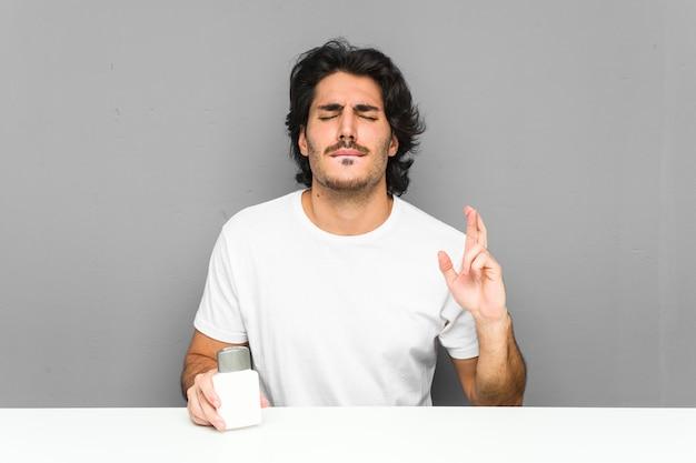 Junger mann, der kreuzungsfinger einer aftershave-creme für das haben des glücks hält