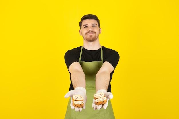 Junger mann, der kuchenrollen mit den händen hält und dir die kamera zeigt.