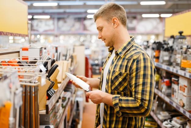 Junger mann, der küchenmesser im haushaltswarengeschäft wählt. männliche person, die haushaltswaren im markt kauft, kerl im küchengeschirrversorgungsgeschäft