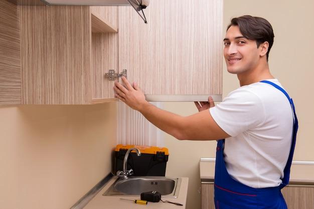 Junger mann, der küchenmöbel zusammenbaut
