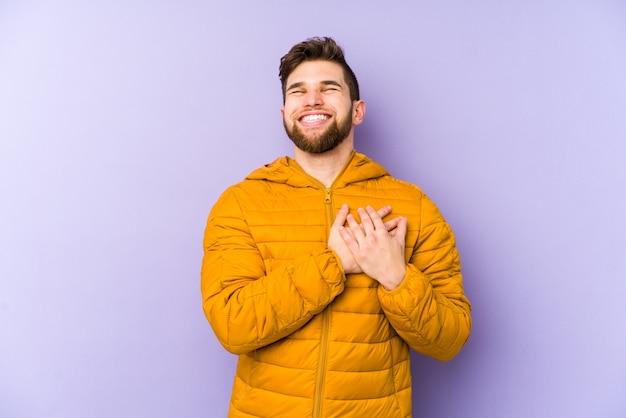 Junger mann, der lachend hände auf herz hält, konzept des glücks.