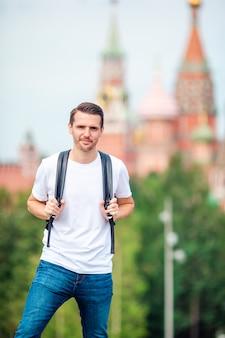 Junger mann, der lächelndes glückliches porträt wandert. männlicher wanderer, der in die stadt geht