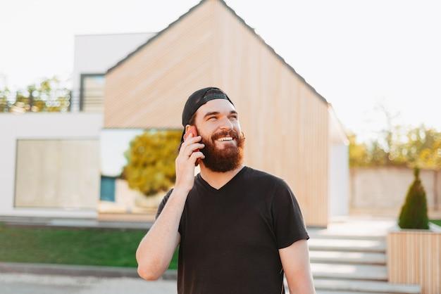 Junger mann, der lächelt und mit seinem telefon spricht und vor seinem neuen haus wegschaut