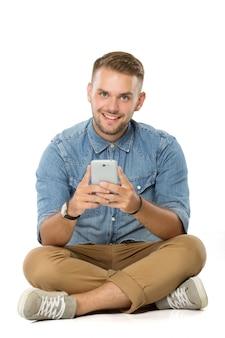 Junger mann, der lächelt, während er sein handy hält, isoliert auf dem boden sitzt
