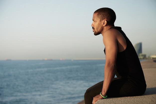Junger mann, der landschaft am strand bewundert