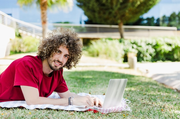 Junger mann, der laptop auf parkboden verwendet