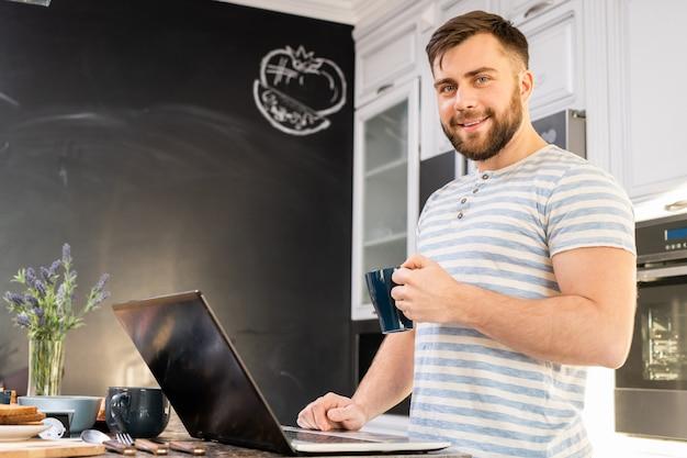 Junger mann, der laptop beim frühstück benutzt