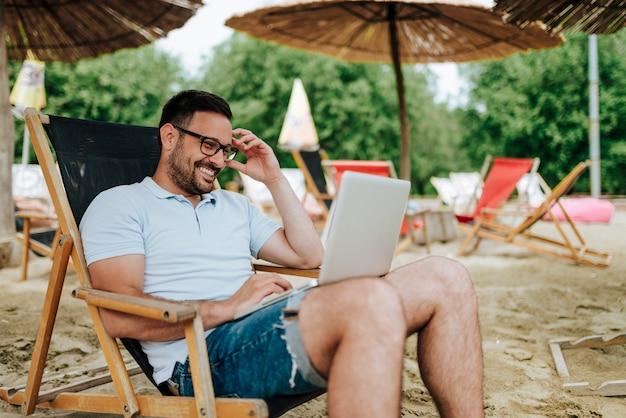 Junger mann, der laptop beim sitzen auf einem strandstuhl verwendet.