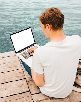 Junger mann, der laptop durch das wasser verwendet