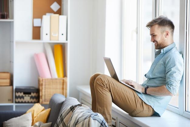 Junger mann, der laptop durch fenster verwendet