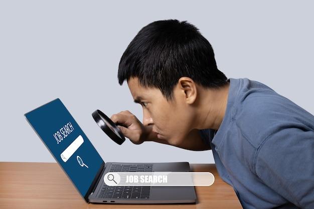 Junger mann, der laptop mit lupe zur jobsuche beobachtet. konzept der stellensuche.