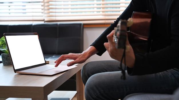 Junger mann, der laptop verwendet und gitarre im wohnzimmer spielt.