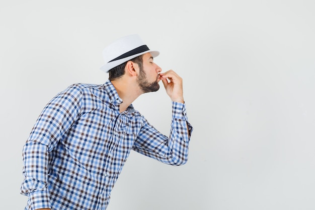 Junger mann, der leckere geste zeigt, indem er finger in kariertem hemd, hut küsst und entzückt aussieht. vorderansicht.