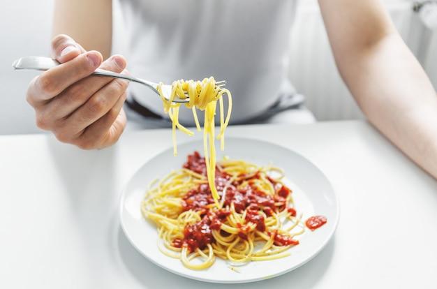 Junger mann, der leckere spaghetti mit tomatensauce isst. nahansicht.