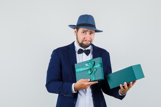 Junger mann, der leere geschenkbox in anzug, hut hält und enttäuscht schaut, vorderansicht.