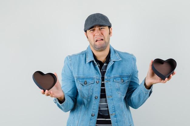 Junger mann, der leere geschenkbox in jacke, mütze zeigt und traurig, vorderansicht schaut.