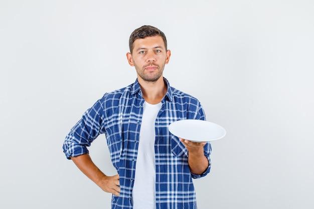 Junger mann, der leere platte mit hand auf taille im hemd, vorderansicht hält.