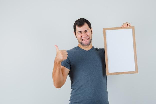 Junger mann, der leeren rahmen hält, der daumen oben im grauen t-shirt zeigt und fröhlich schaut