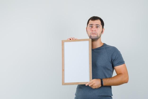 Junger mann, der leeren rahmen im grauen t-shirt hält und beunruhigt aussieht