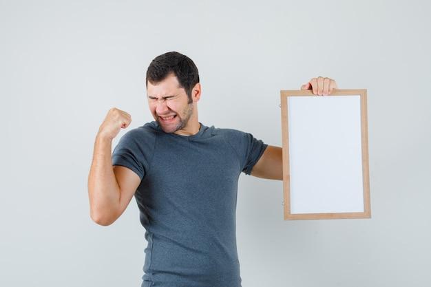 Junger mann, der leeren rahmen im grauen t-shirt hält und glück schaut