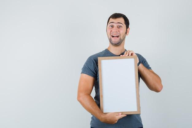 Junger mann, der leeren rahmen im grauen t-shirt hält und glücklich schaut