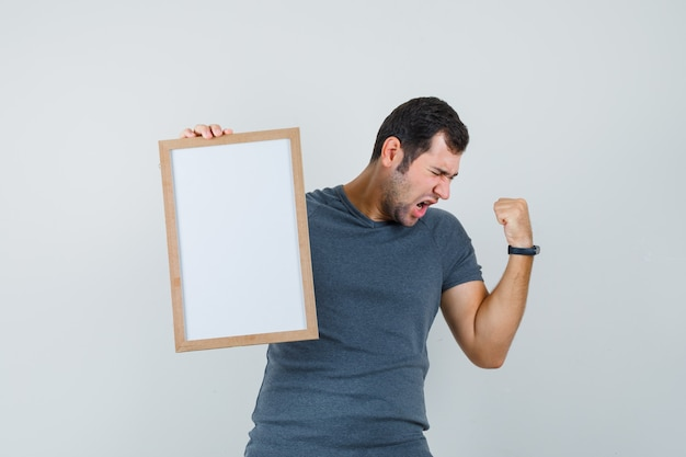 Junger mann, der leeren rahmen im grauen t-shirt hält und glückselig schaut