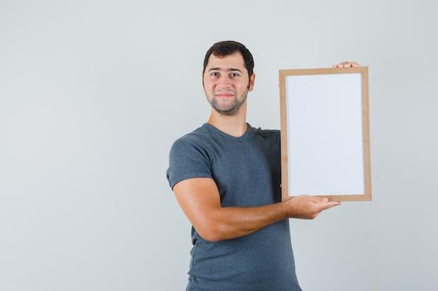Junger mann, der leeren rahmen im grauen t-shirt hält und zuversichtlich schaut