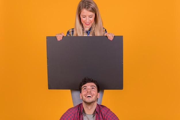 Junger mann, der leeren schwarzen plakatgriff von ihrer freundin gegen einen orange hintergrund betrachtet