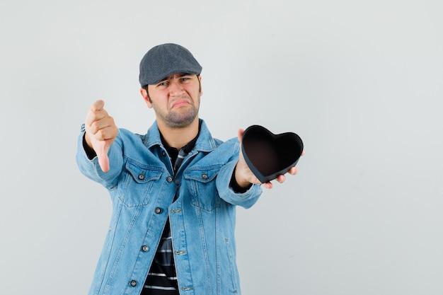 Junger mann, der leeres geschenk hält, während daumen unten in jacke, mütze zeigt und verärgert schaut
