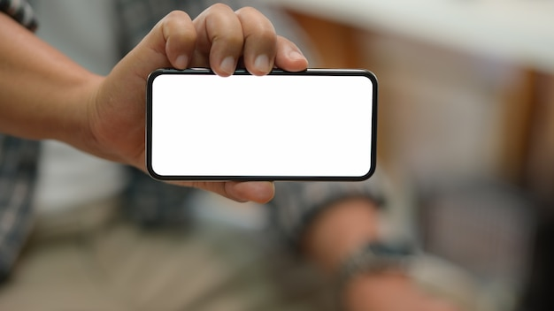 Junger mann, der leeres intelligentes telefon sitzt und zeigt