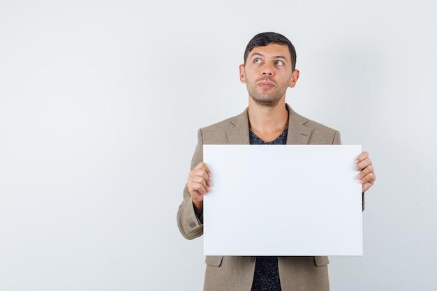 Junger mann, der leeres papier in graubrauner jacke hält und nachdenklich aussieht. vorderansicht.