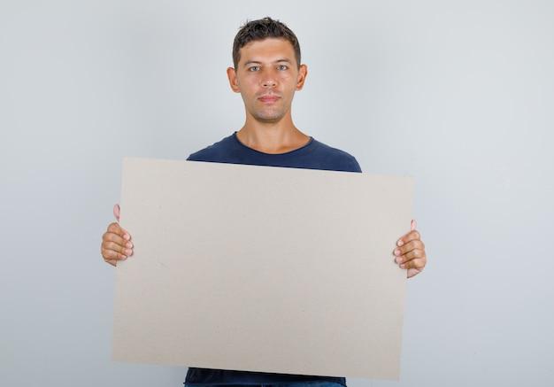 Junger mann, der leeres plakat im dunkelblauen t-shirt hält und hoffnungsvoll schaut. vorderansicht.